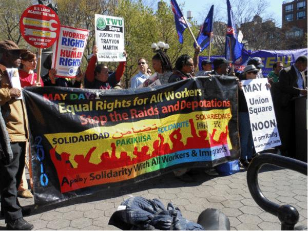 May Day March with banner saying 'Equal Rights for all workers! Stop the raids and deportations!'